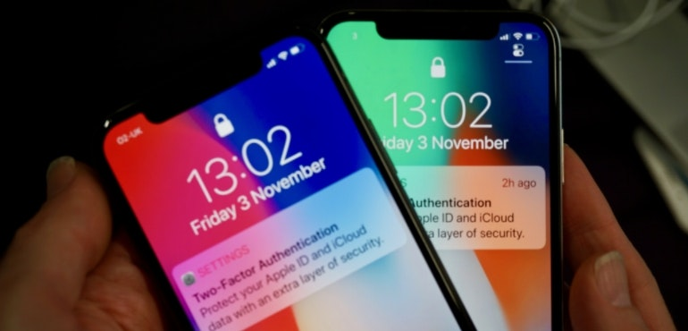 iPhone X two handsets in-hand hero size