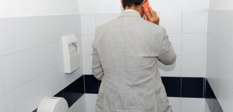 Man using smartphone in the toilet