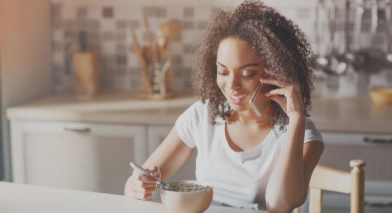 Woman talking on phone at breakfast